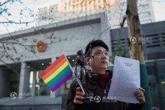 Yang Teng gay dari Beijing memegang bendera homo, patung Lady Justice dan hasil pengadilan